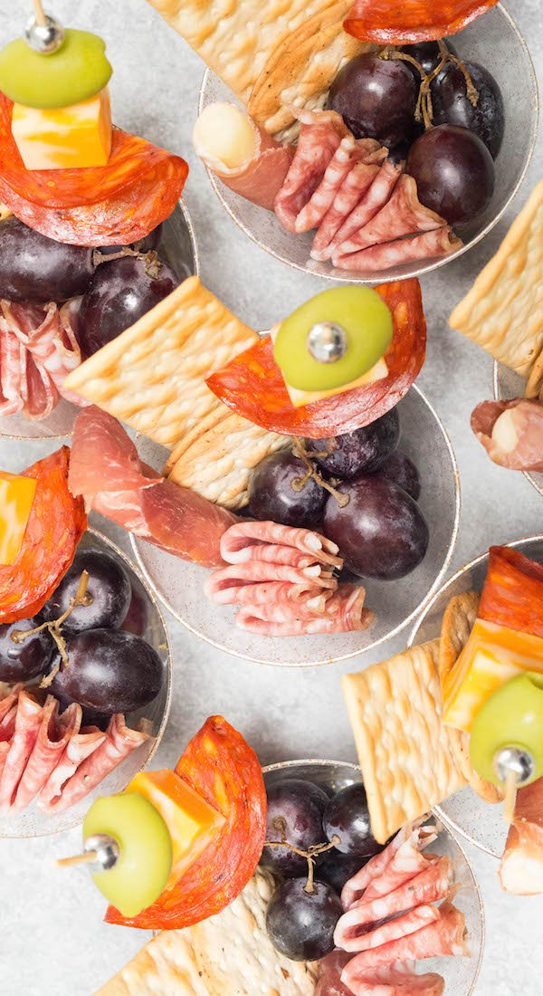 Overhead shot of plastic cups filled with meat, cheese, and grapes on a light background.
