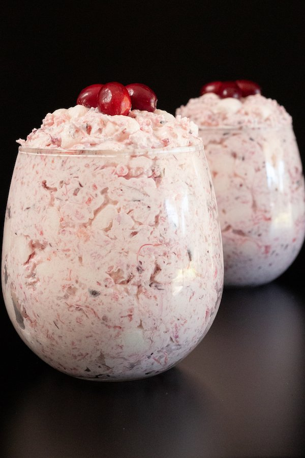 Two stemless wine glasses filled with cranberry fluff dessert on a black background