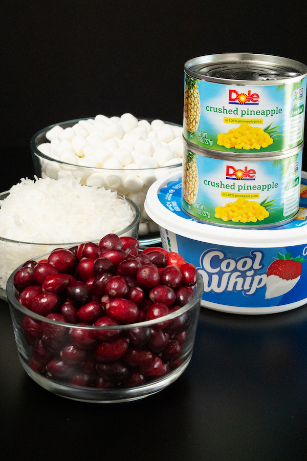 A tub of cool whip, two cans of crushed pineapple, a bowl of fresh cranberries, coconut, and mini marshmallows sit on a black background to show the ingredients needed for cranberry fluff