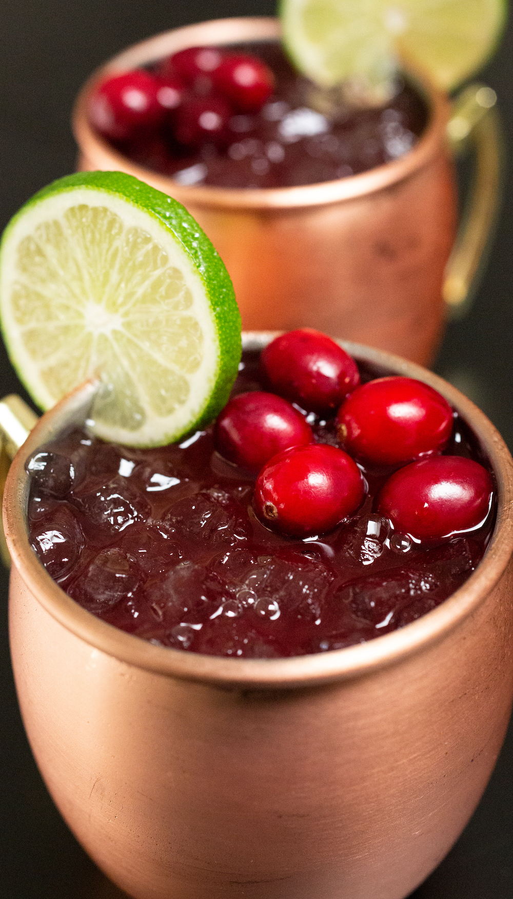 Two copper mules filled with cranberry moscow mules sit on a black background. They are each garnished with a lime wheel and fresh cranberries.