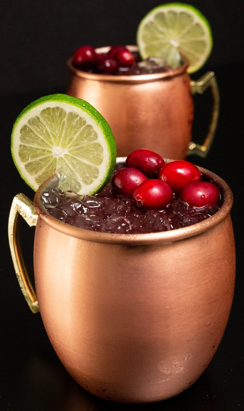 Wide shot of two cranberry moscow mules in copper mugs sitting on a black background.
