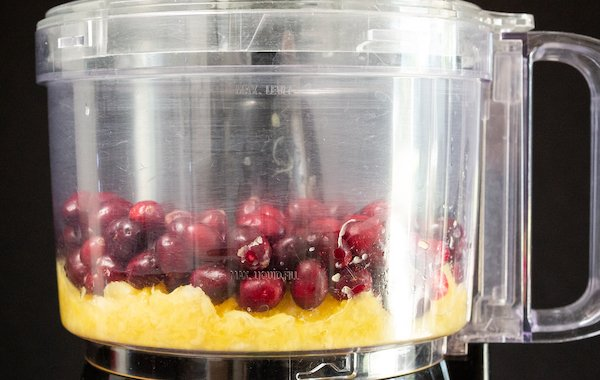 Fresh cranberries and crushed pineapple sit in a food processor on a black background