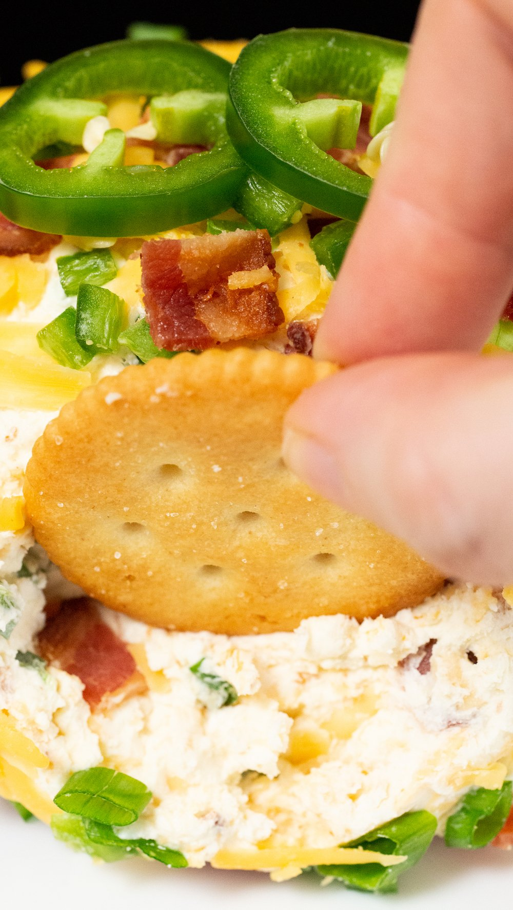 Close up of a ritz cracker being dipped in a jalapeno popper cheese ball