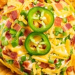 Overhead shot of a jalapeno popper cheeseball covered in shredded cheddar, diced jalapeños, and chopped bacon