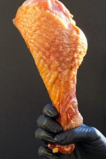 A hand holds a very large smoked turkey leg in front of a black electric smoker