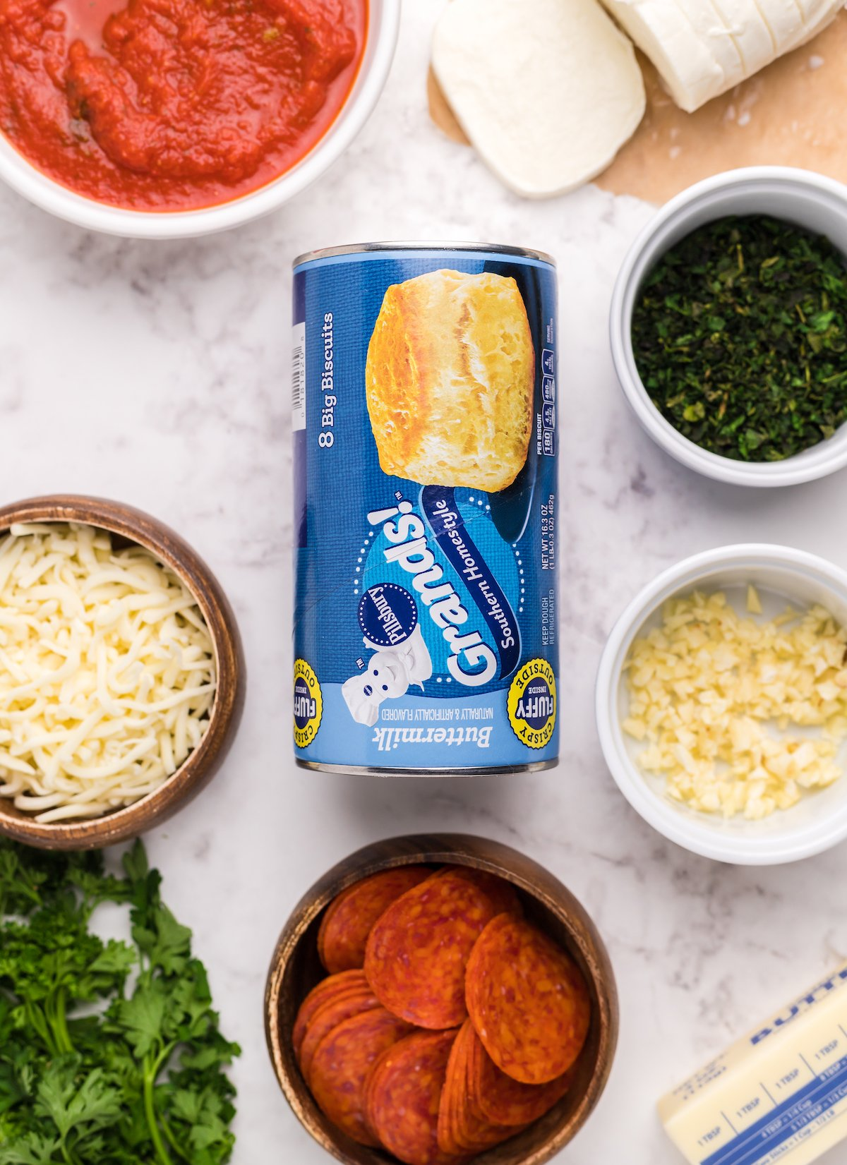 Overhead look at the ingredients to make biscuit pizza casserole: canned Grands! Biscuits, shredded mozzarella, fresh mozzarella, pepperonis, butter, minced garlic, and parsley.
