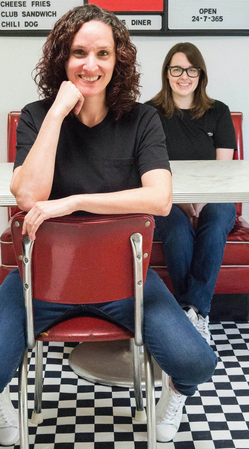 Two women sit at a diner table with a red booth, red chair, and black and white checkered floor