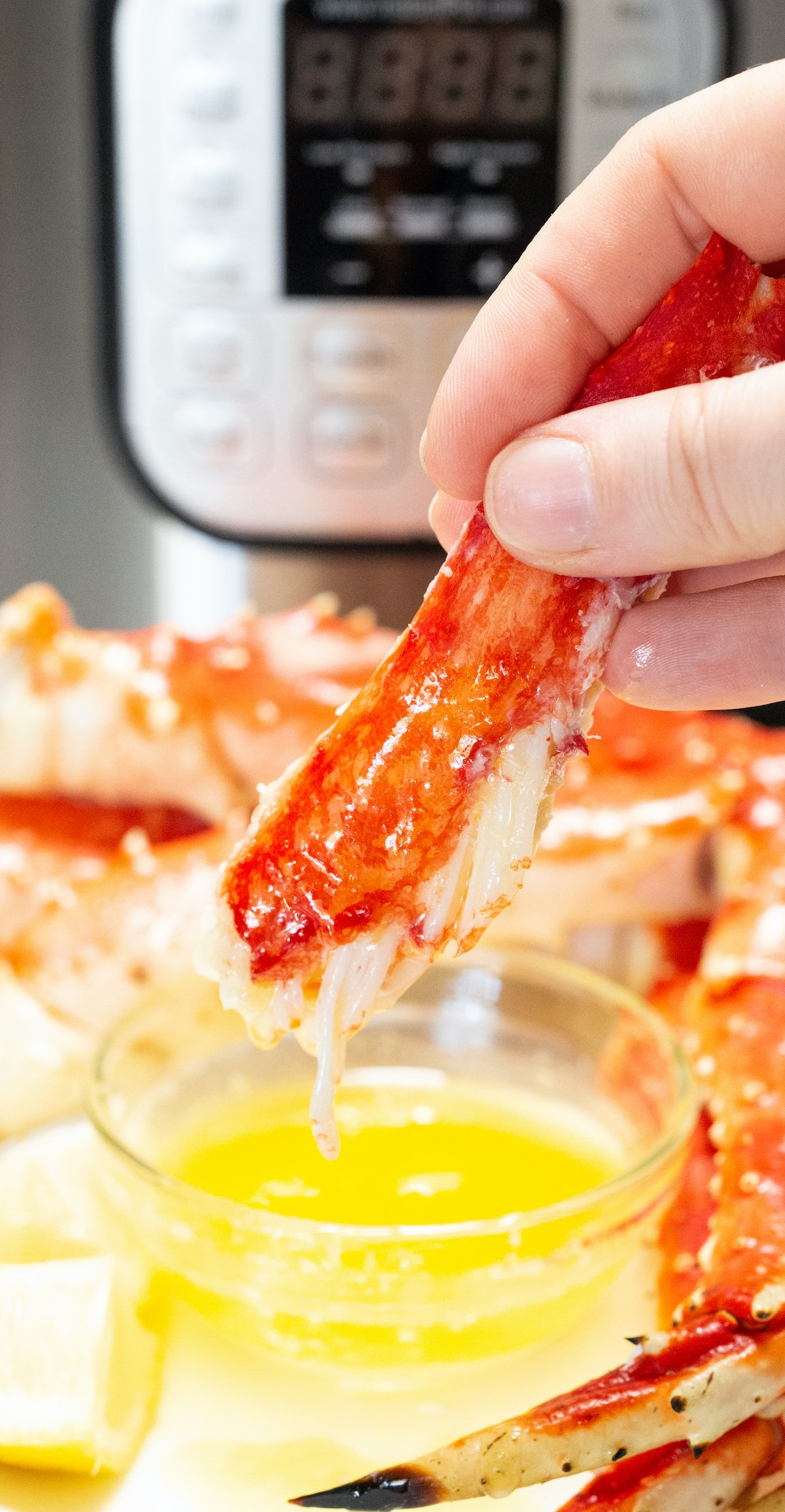 Crab leg meat is being dipped in a bowl of butter that is sitting in front of an Instant Pot
