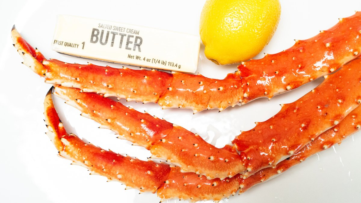 A cluster of king crab legs sit on a white platter next to a stick of butter and a lemon