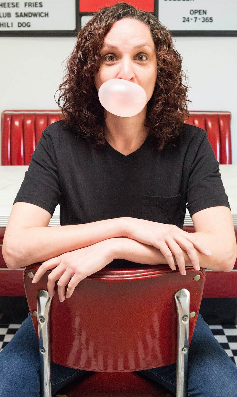 A women in a black t-shirt sits at a red diner chair and blows a bubble of pink bubblegum