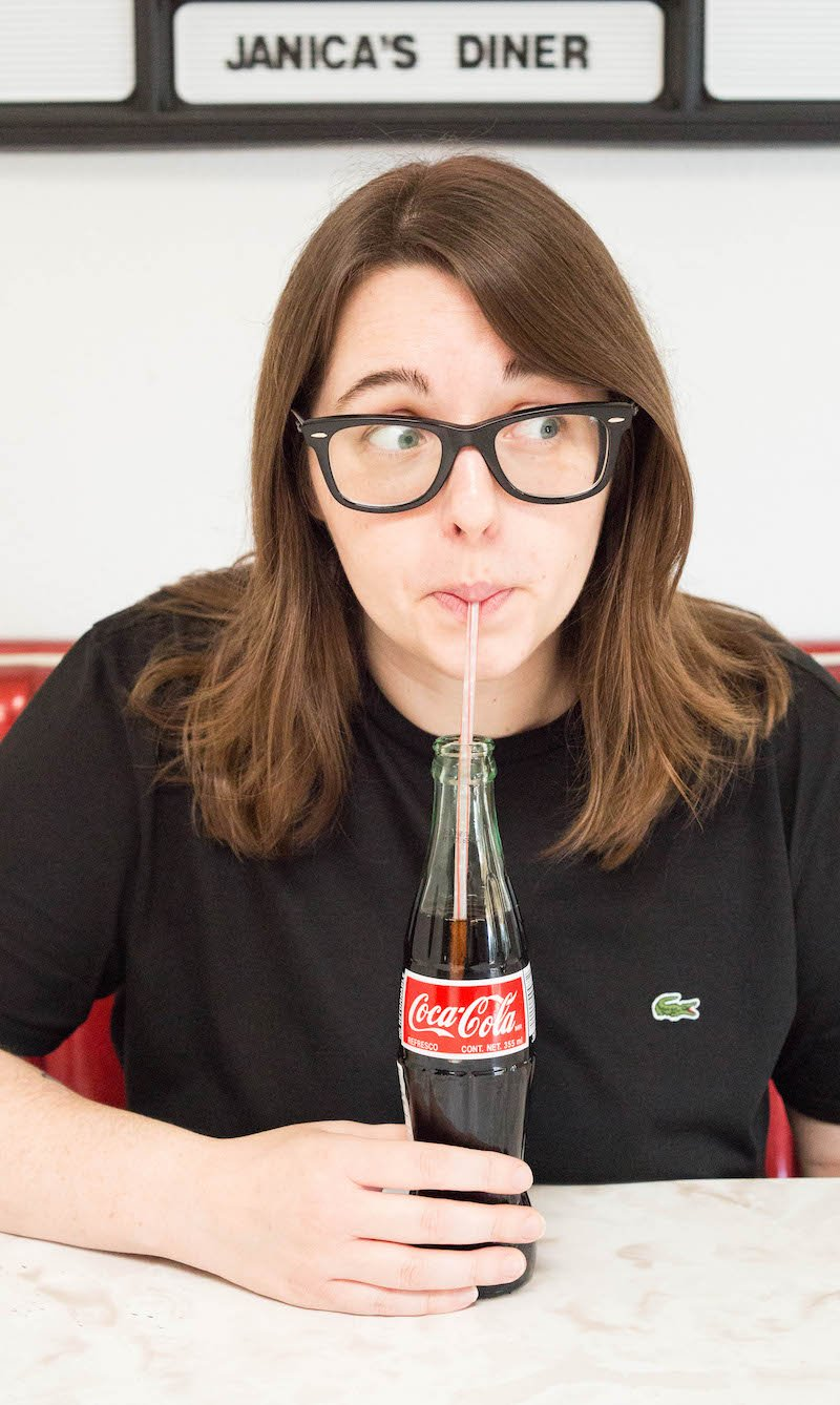 A woman in a black t-shirt sips on a coke in a bottle while sitting at a diner table