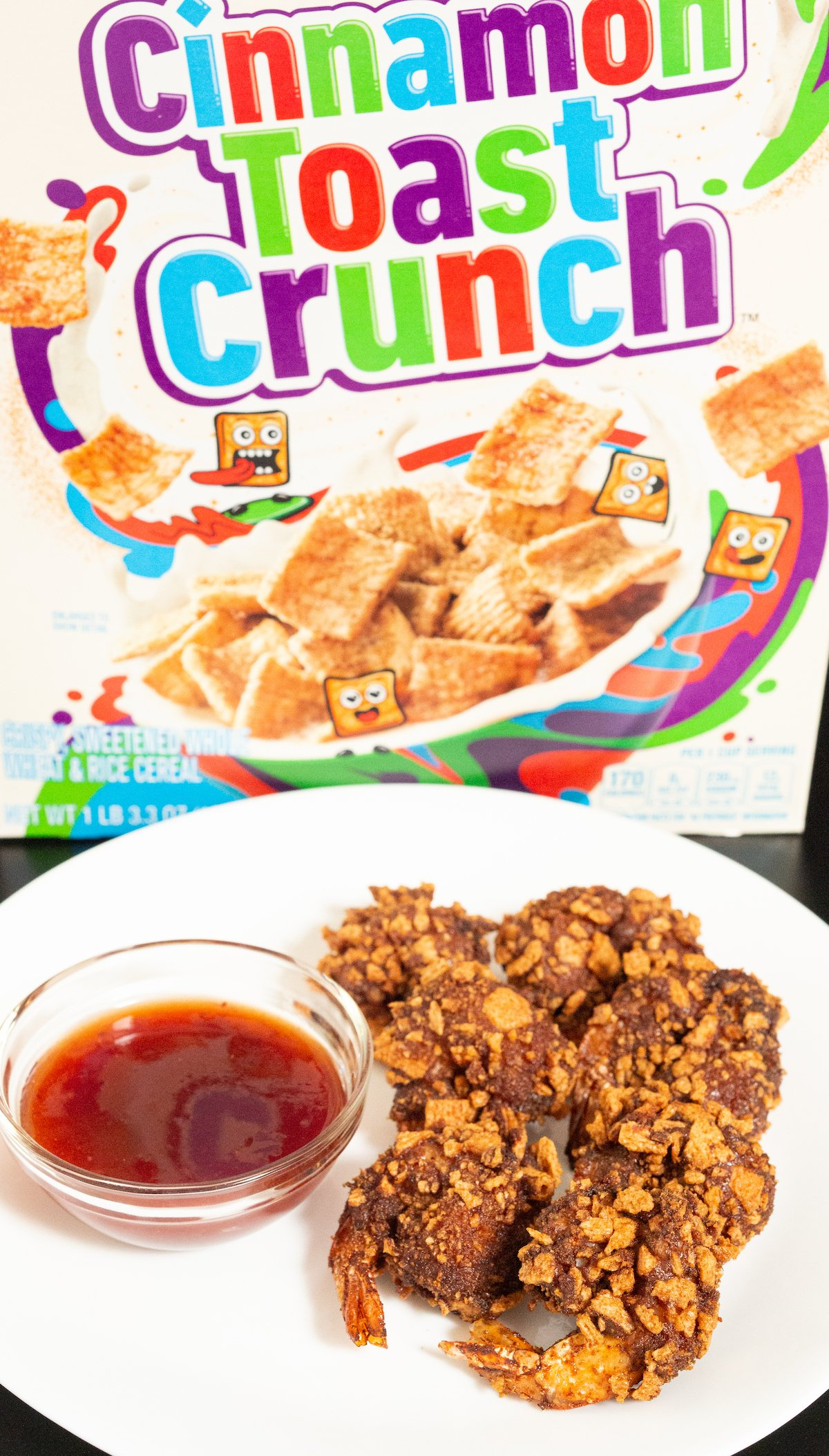 Six Cinnamon Toast Crunch battered and fried shrimp sit on a white plate next to strawberry habanero dipping sauce and in front of a Cinnamon Toast Crunch cereal box.