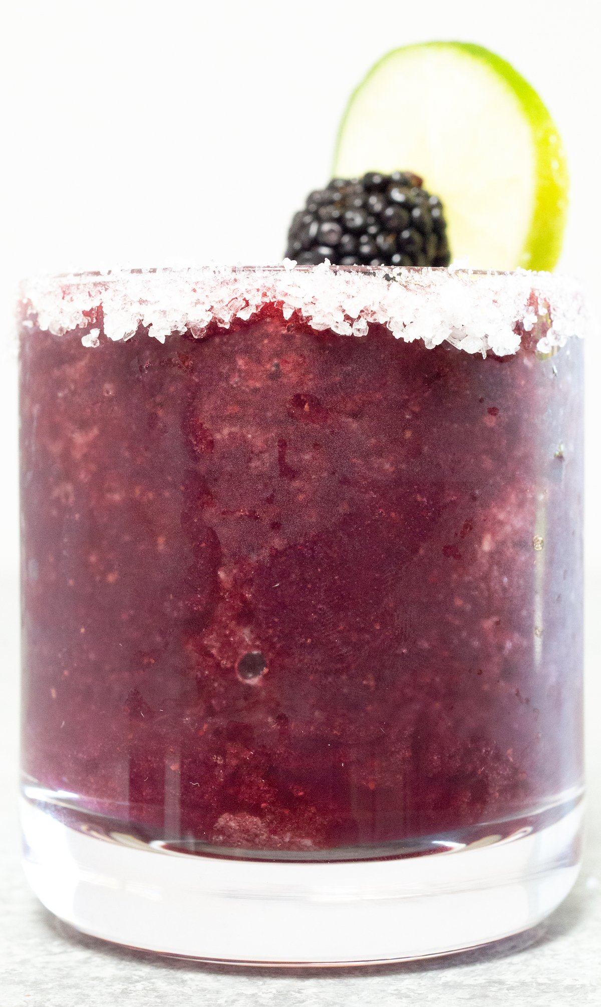 A glass filled with a purple blackberry margarita sits on a white background.