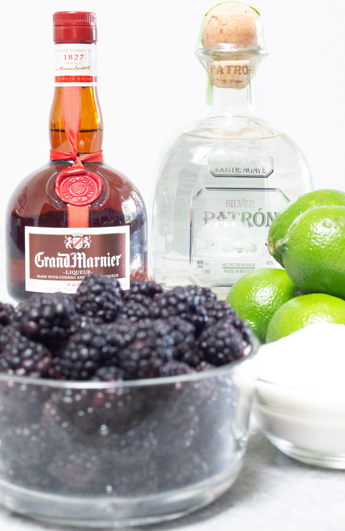 The ingredients for blackberry margaritas on a white background. Grand marnier, Patron, blackberries, limes, and sugar.
