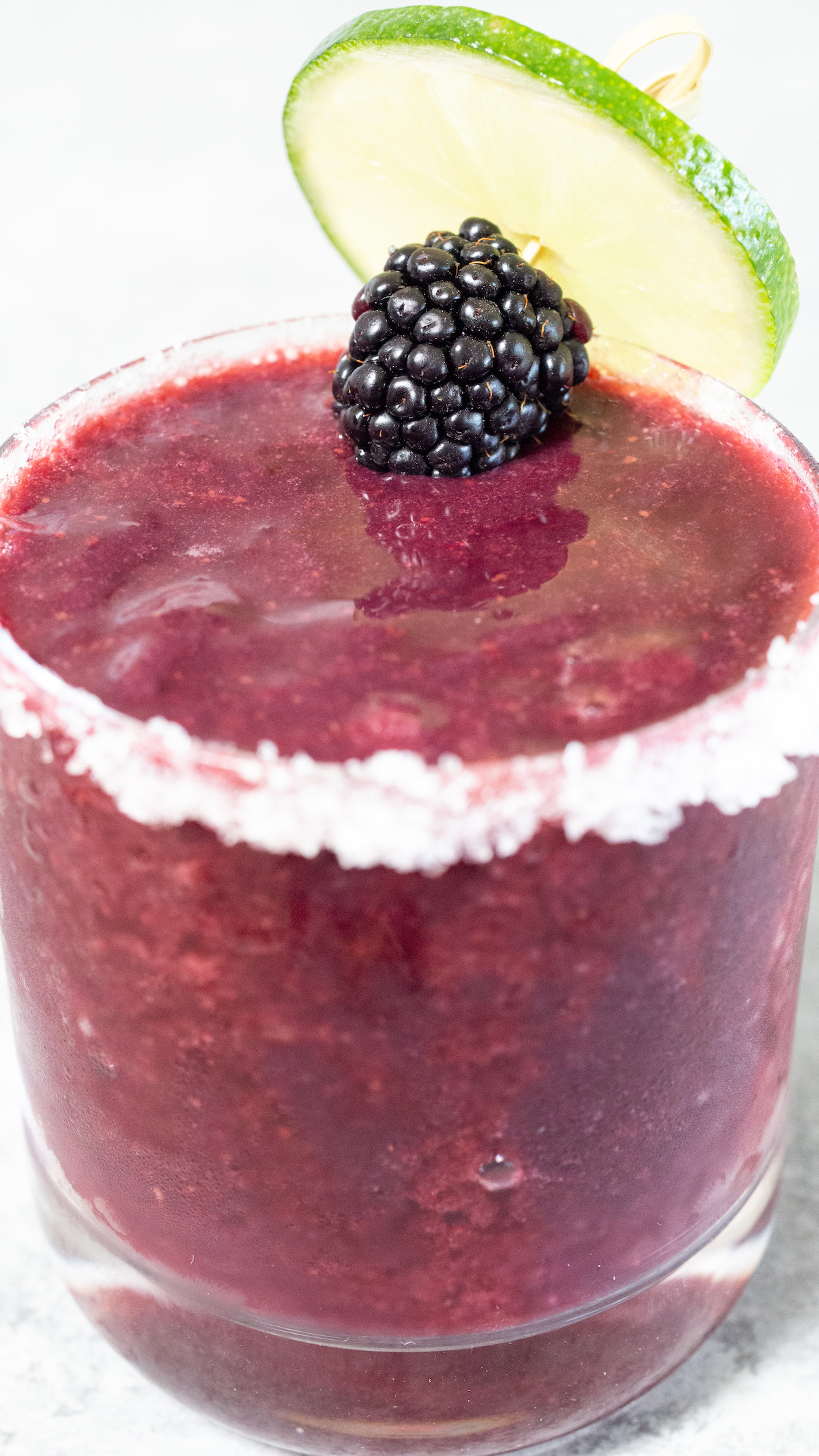 A purple blackberry margarita in a short glass garnished with a blackberry and lime wheel.