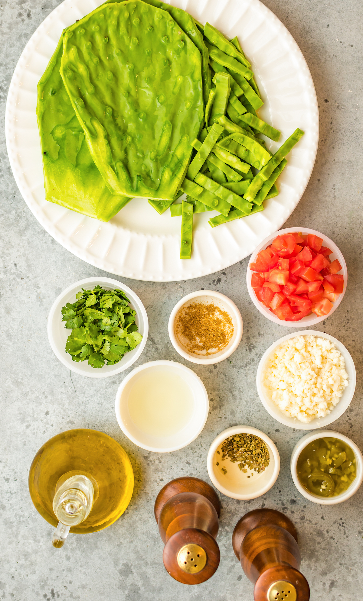 Overhead view of the ingredients for cactus salad arranged in white prep bowls: fresh cactus paddles, cilantro, cumin, chopped tomatoes, queso fresco, oregano, pickled jalapenos, salt, pepper, and olive oil.