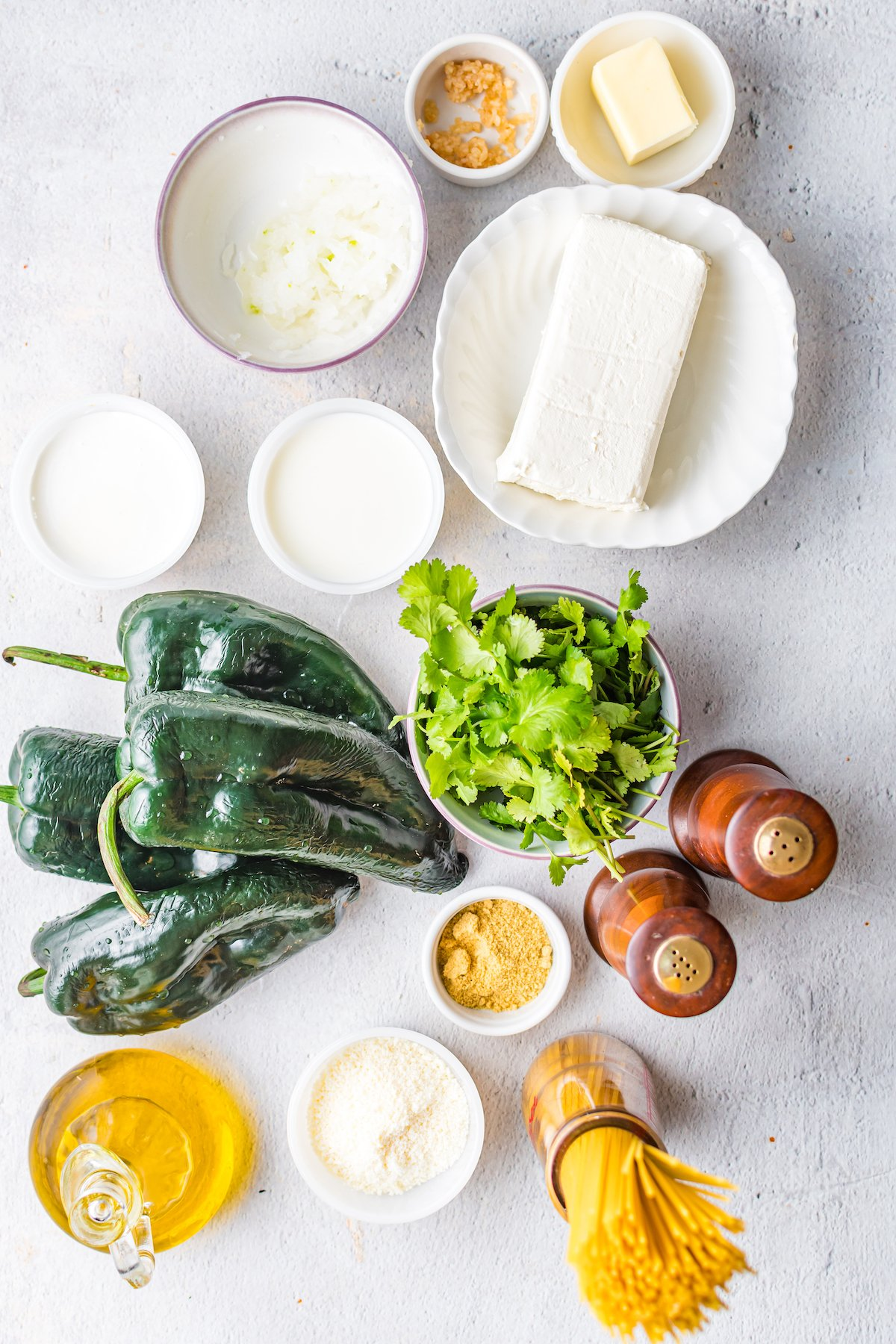 Overhead shot of the ingredients you need to make green Mexican spaghetti. Fresh poblanos, cream cheese, cilantro, noodles, salt, pepper, and oil.