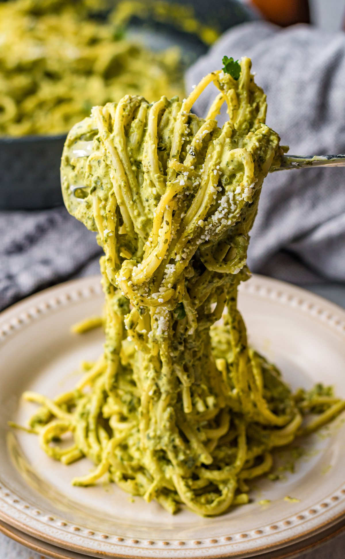 A fork twirls green Mexican spaghetti over a plate