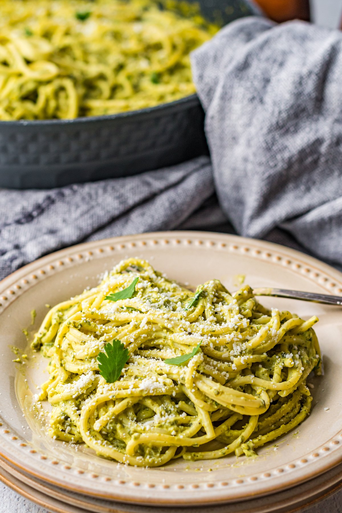 A dinner plate of green Mexican spaghetti sits in front of a pan filled with it as well