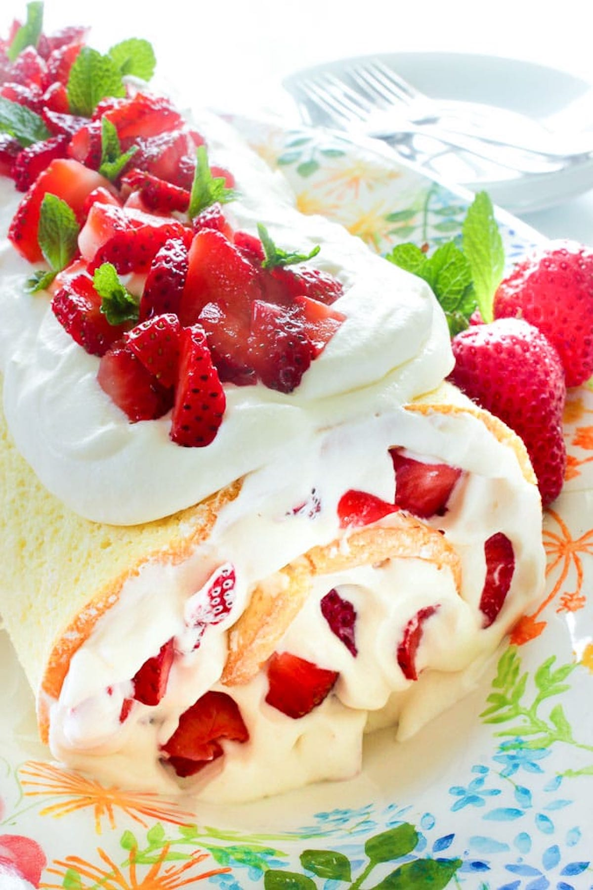 A yellow cake roll filled with cream & strawberries and also topped with strawberries and whipped cream.
