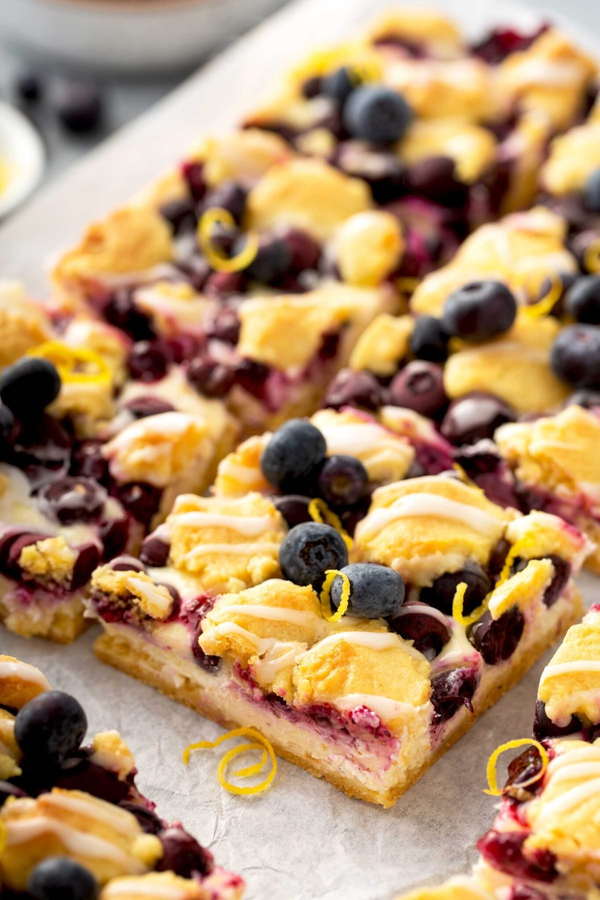 A pan of lemon blueberry cheese cake bars have been cut into squares.
