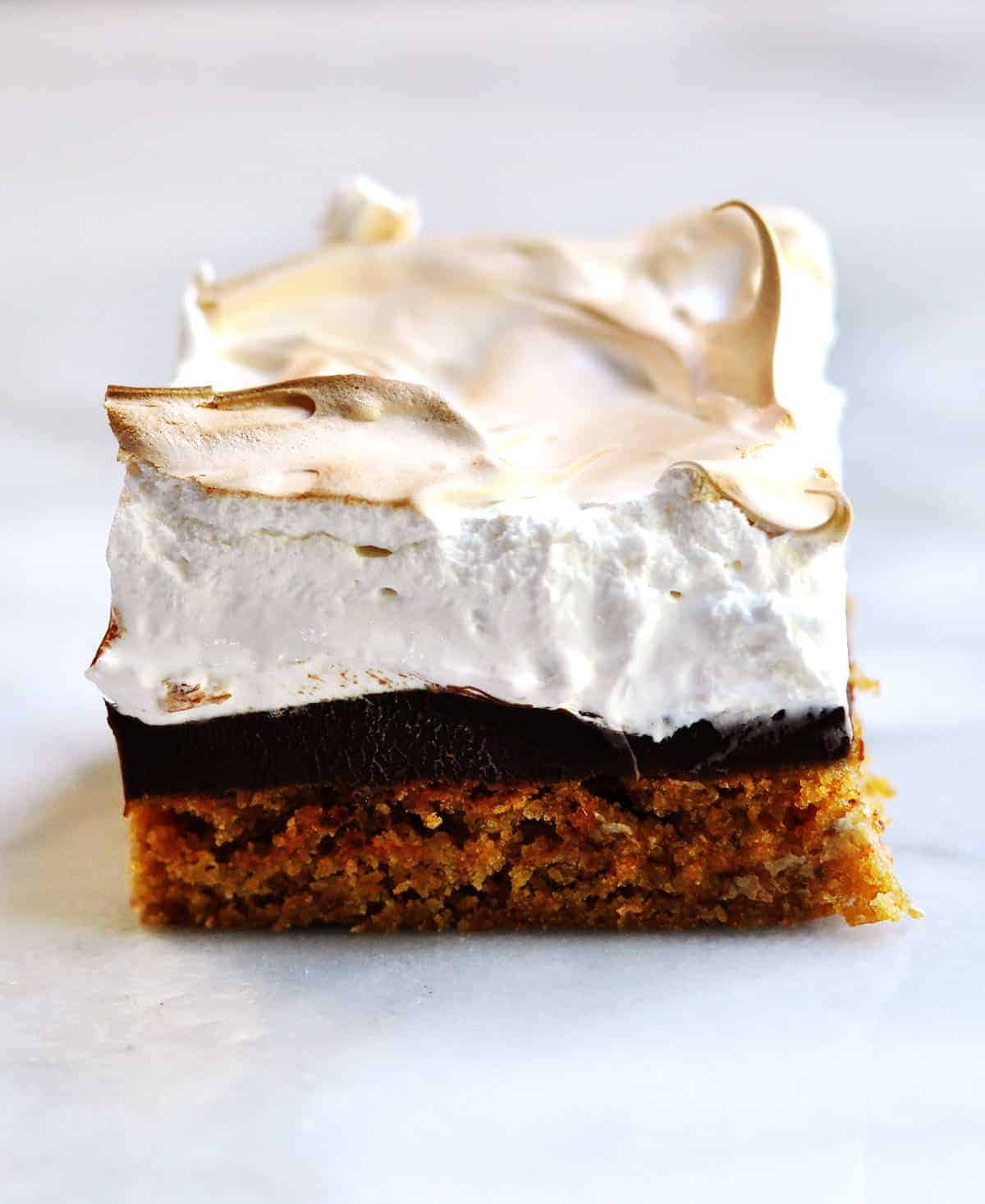A brownie with a clear graham cracker layer, chocolate layer, and toasted marshmallow meringue layer sits on a white background.