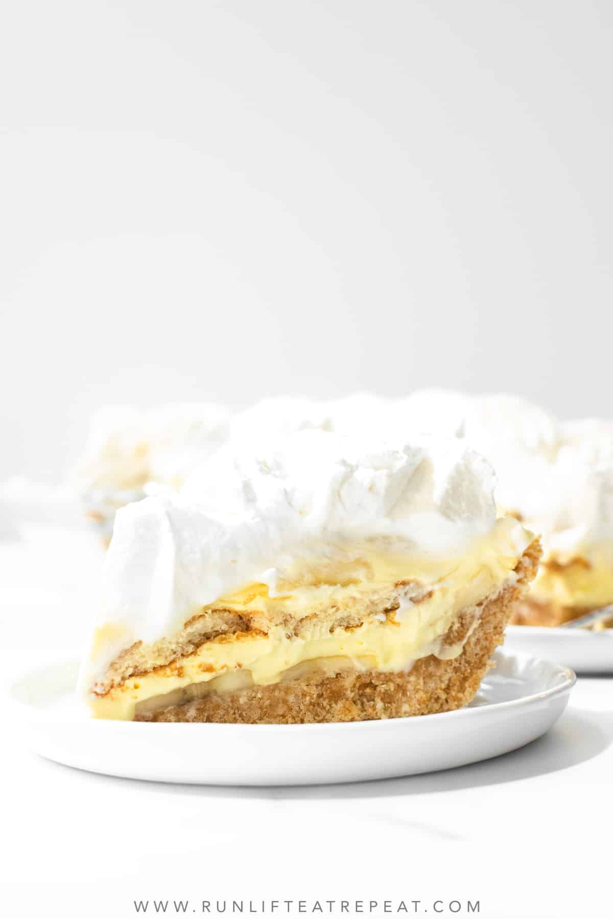 A single slice of banana pudding pie sits on a white serving plate in front of the rest of the pie.