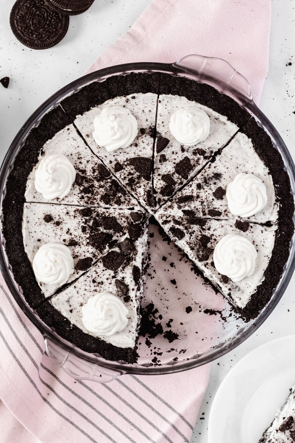 Overhead view of a cookies & cream oreo pie in a glass pie dish. A slice has been removed.