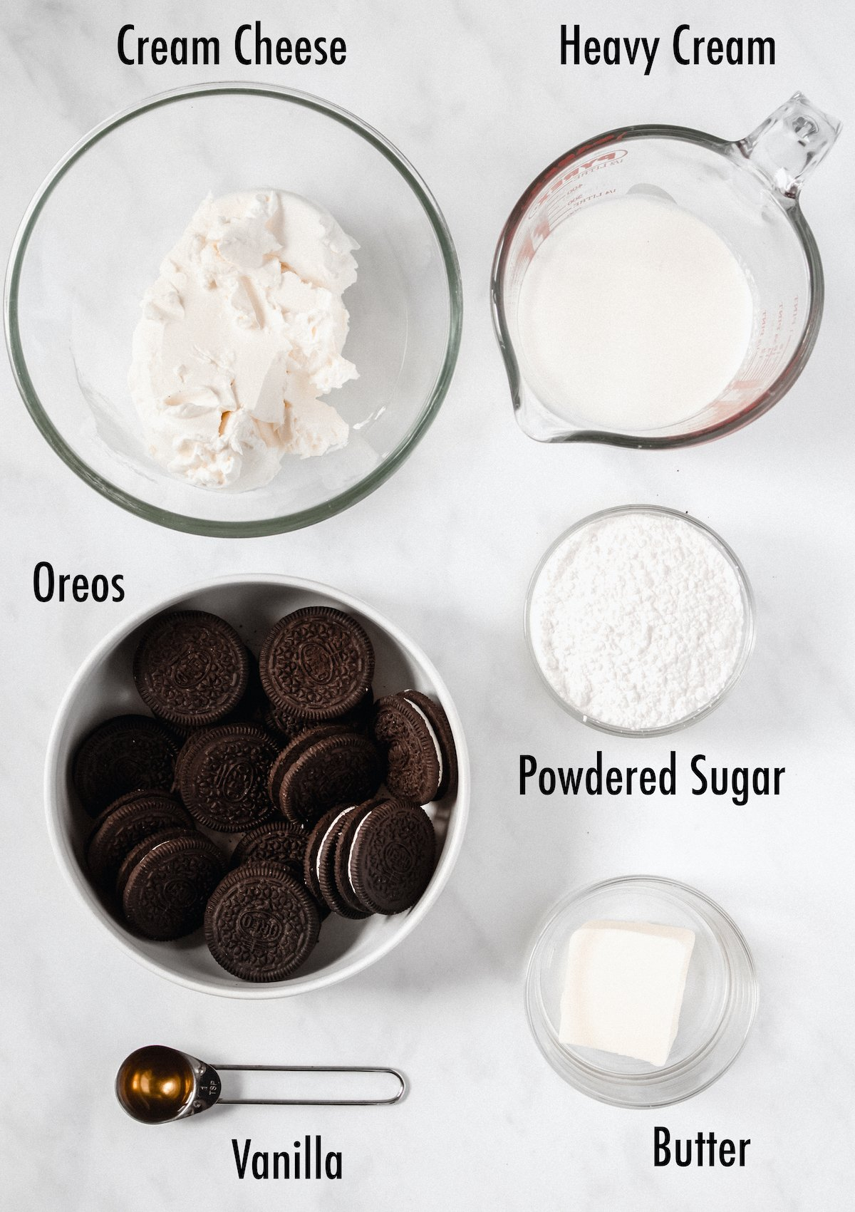 Overhead view of the ingredients needed for cookies and cream pie: cream cheese, heavy cream, oreos, powdered sugar, vanilla, and butter