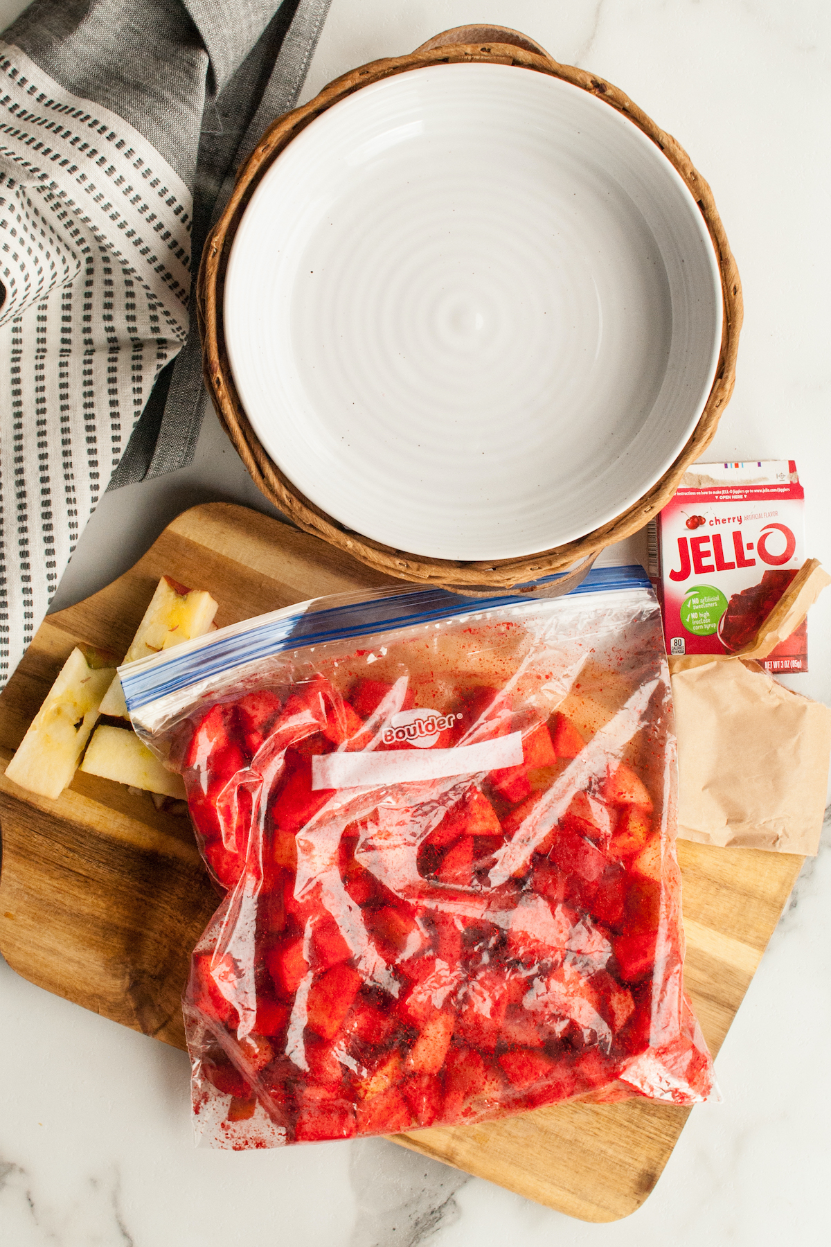 Overhead view of chopped apples that have been put in a ziploc bag and covered with red cherry jello powder