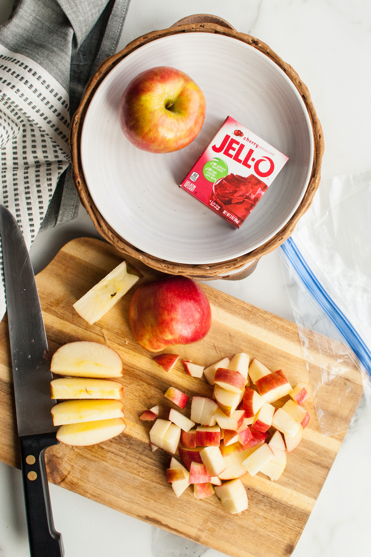 Overhead view of chopped apples on a cutting board next to a box of Jello