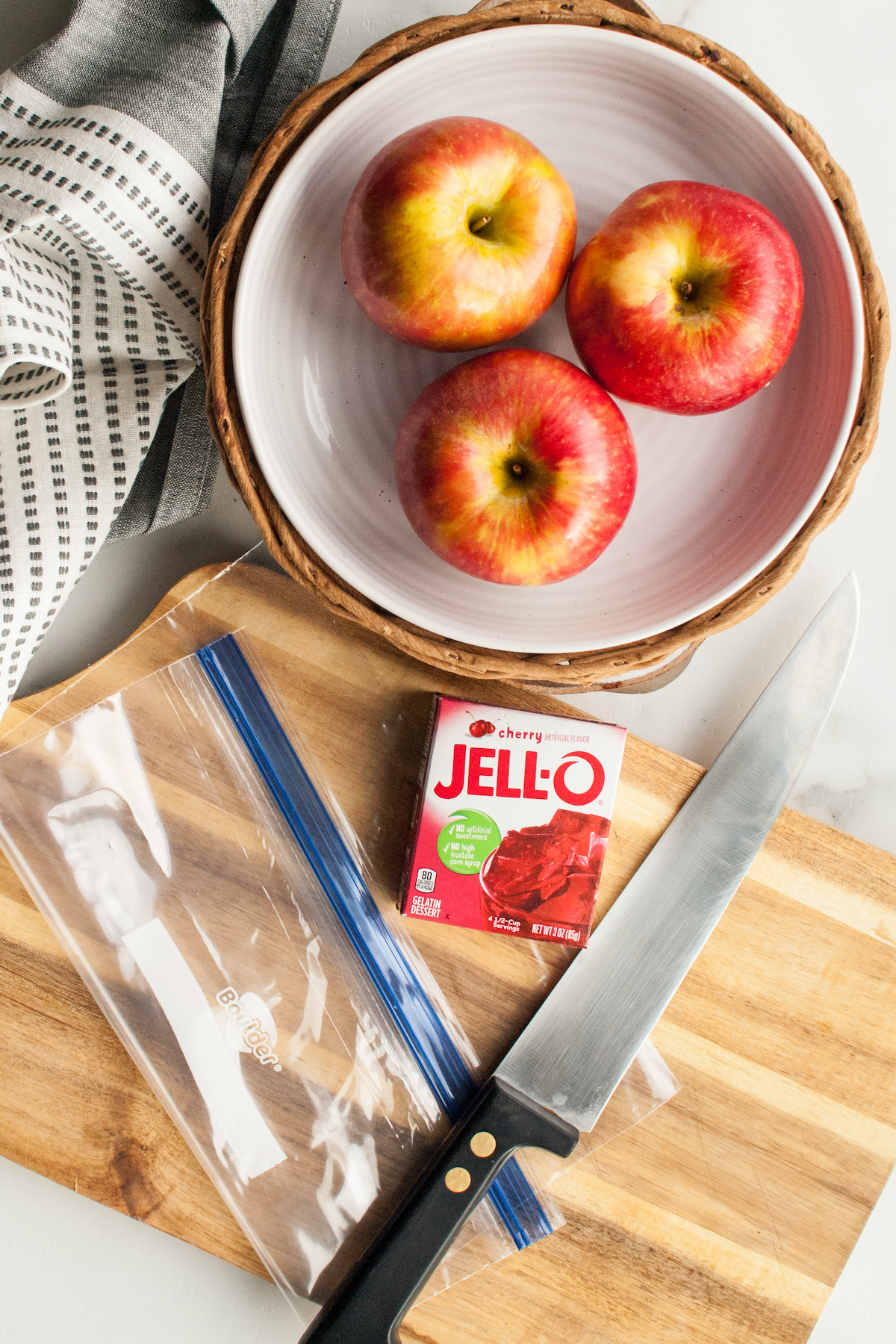 Overhead view of jello apple ingredients (3 apples, 1 box of jello powder) sitting next to a knife, ziploc bag, and a cutting board.