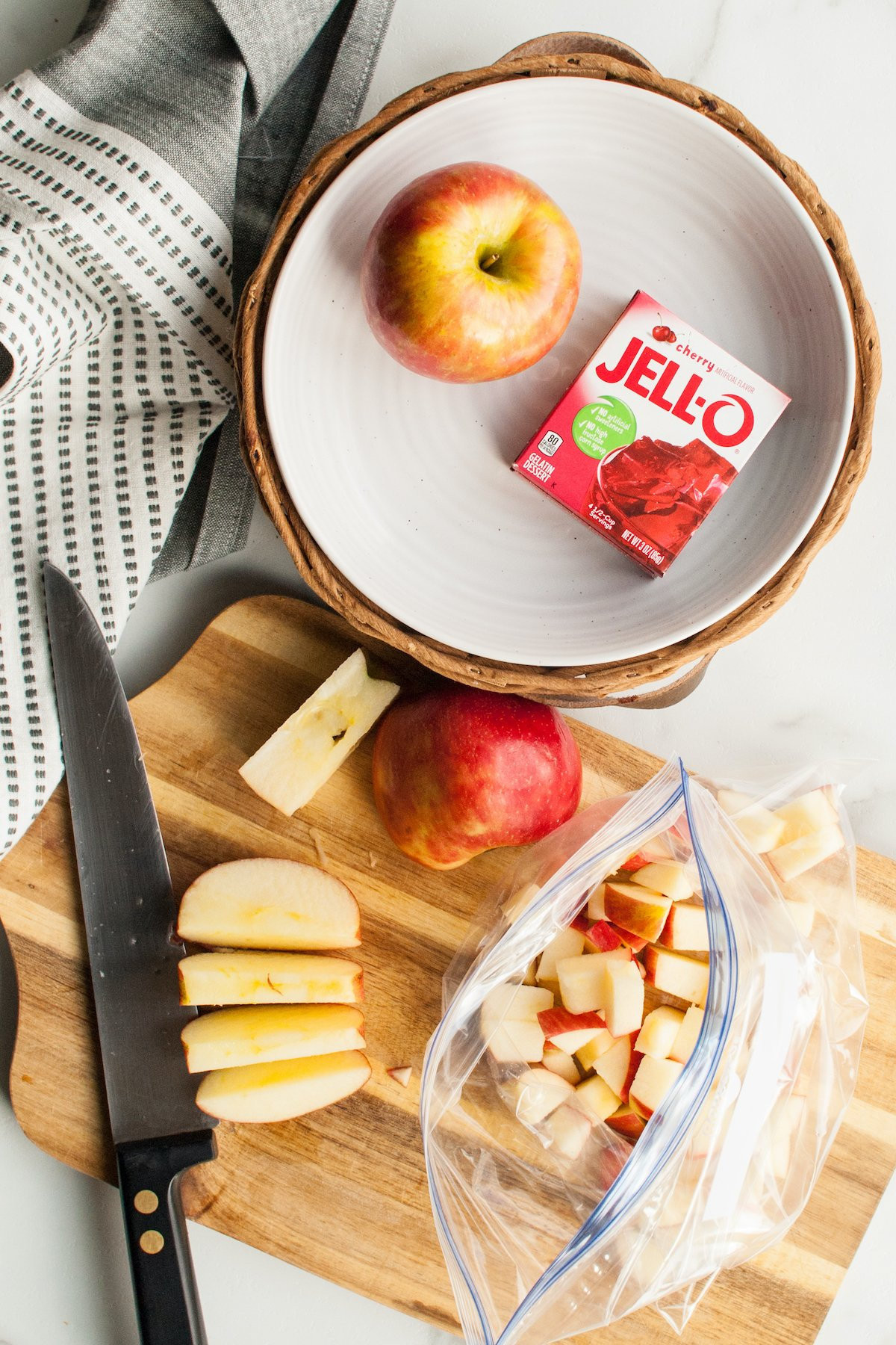 Chopped apples being put into a Ziploc bag.