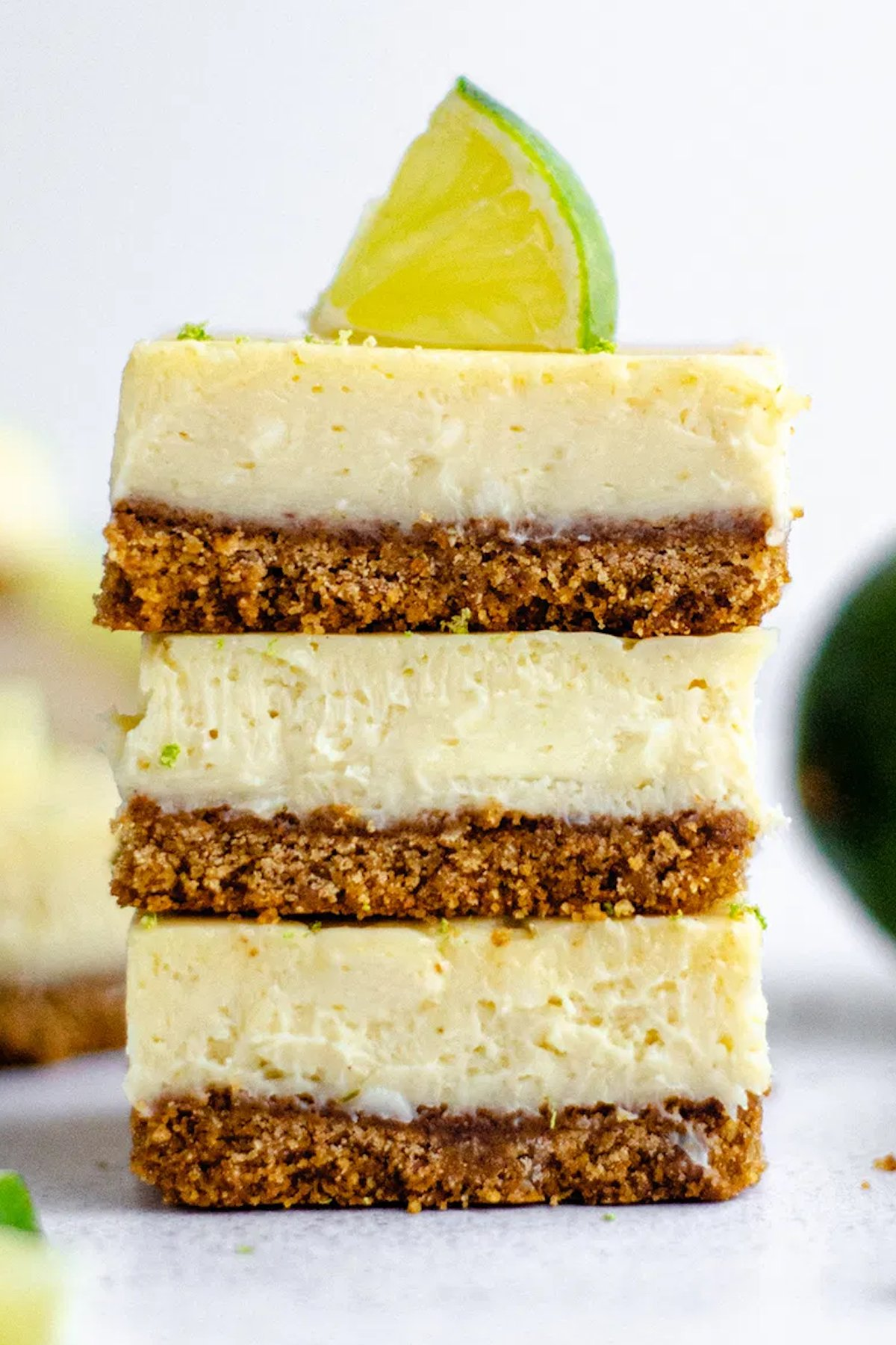 Three key lime pie bars stacked on top of one another on a light background. The top bar is garnished with a lime slice.