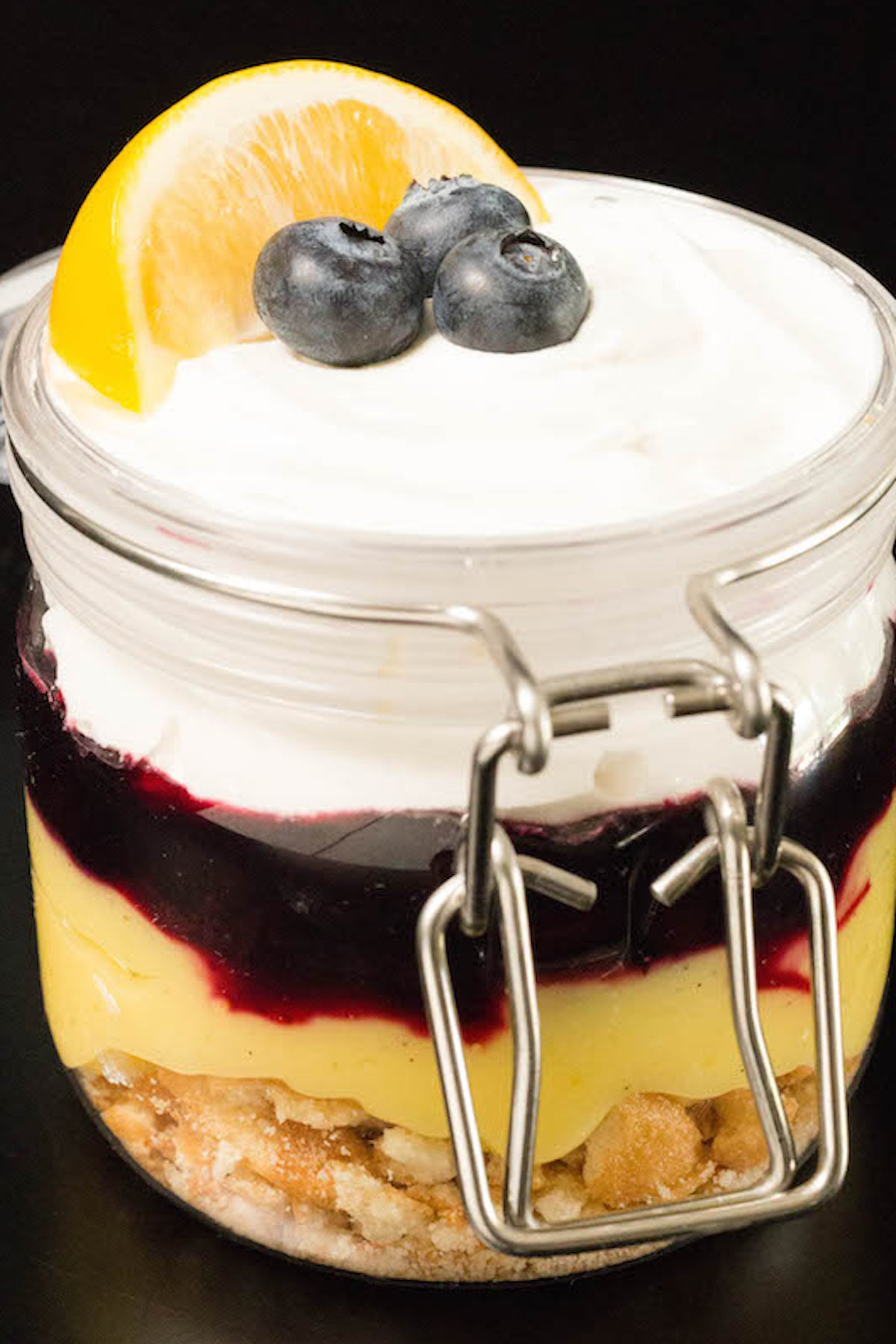 A small glass jar filled with layers of nilla wafers, lemon curd, blueberry compote and whipped cream sits on a black background.