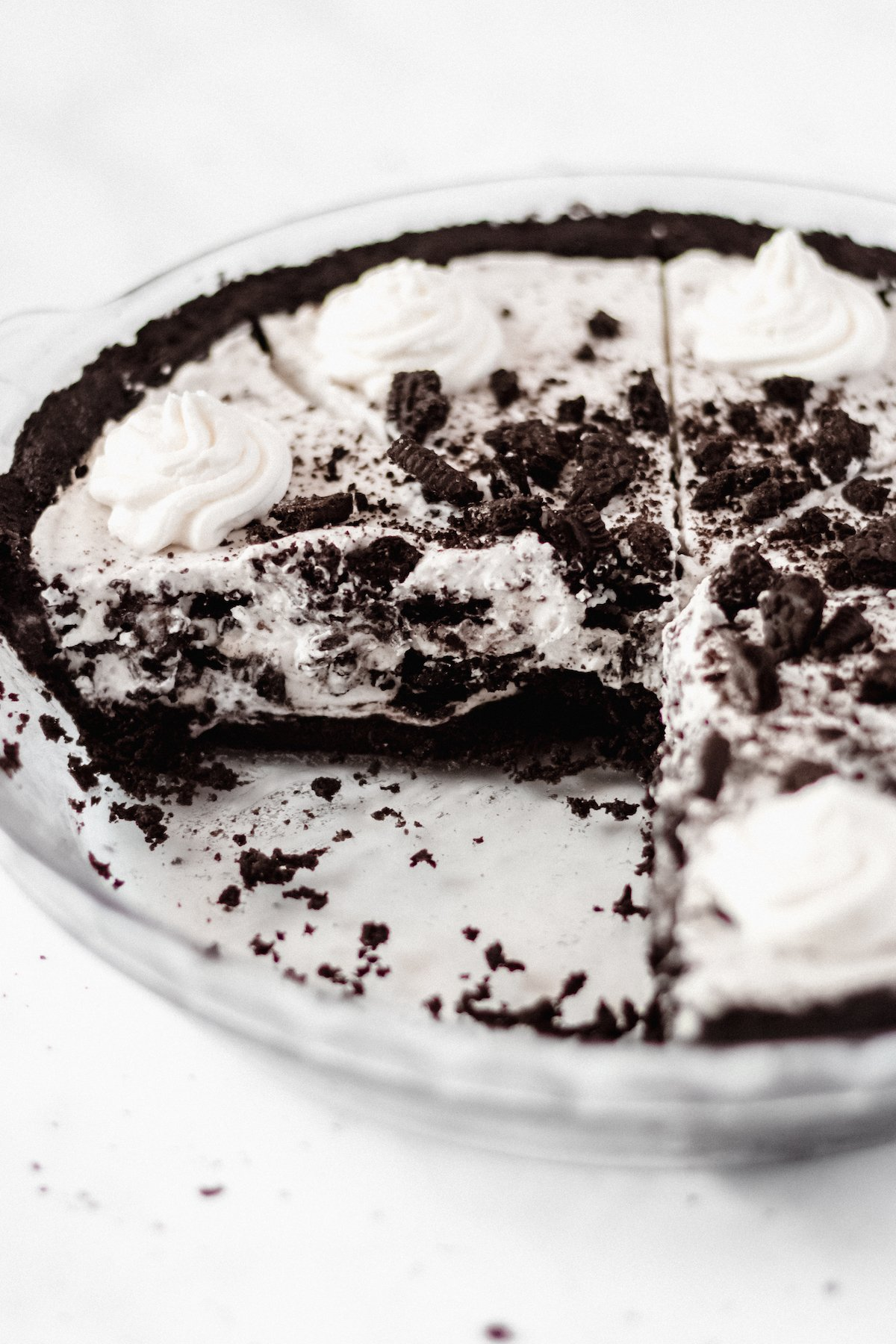 A cookies and cream pie in a glass pie dish on a white background. Two slices have been removed.