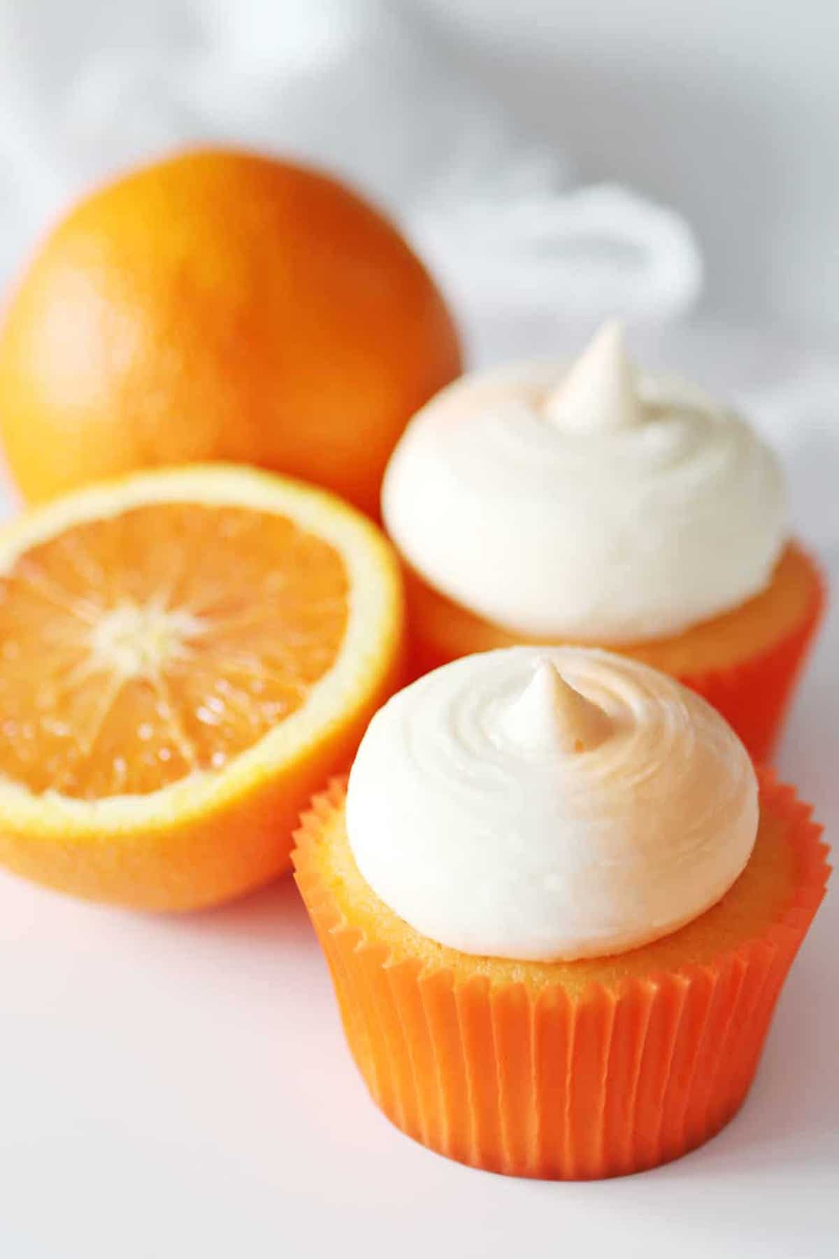 Two orange creamsicle cupcakes topped with white frosting sit on a light background next to an orange that has been sliced in half.