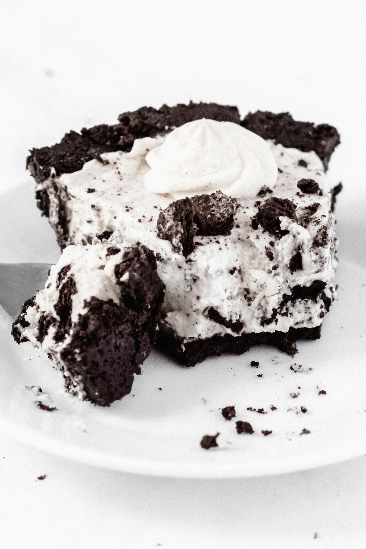 A slice of cookies & cream pie with a forkful taken out of it sits on a white plate on a white background