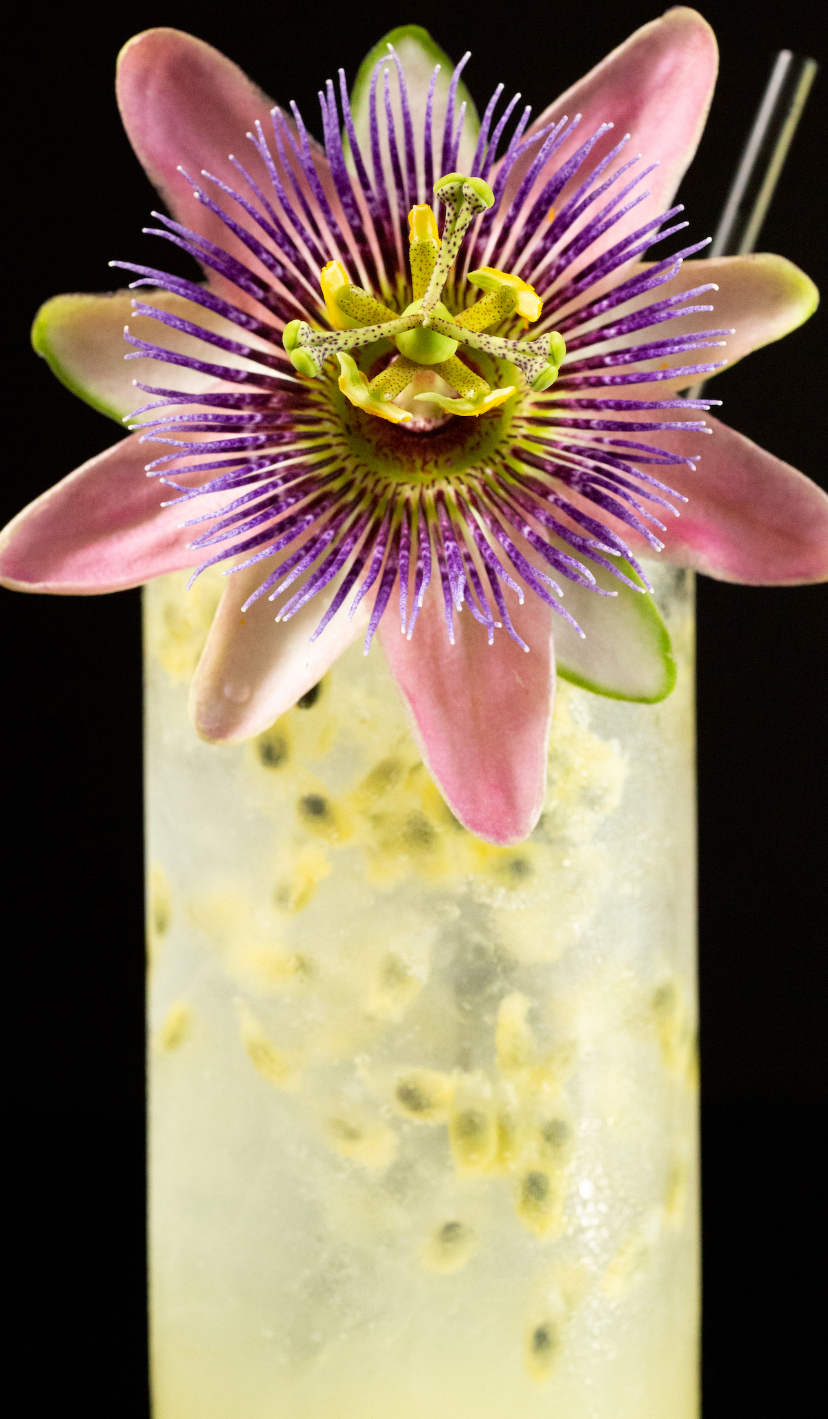 A cocktail with passion fruit puree is garnished with a passion fruit flower and black straw