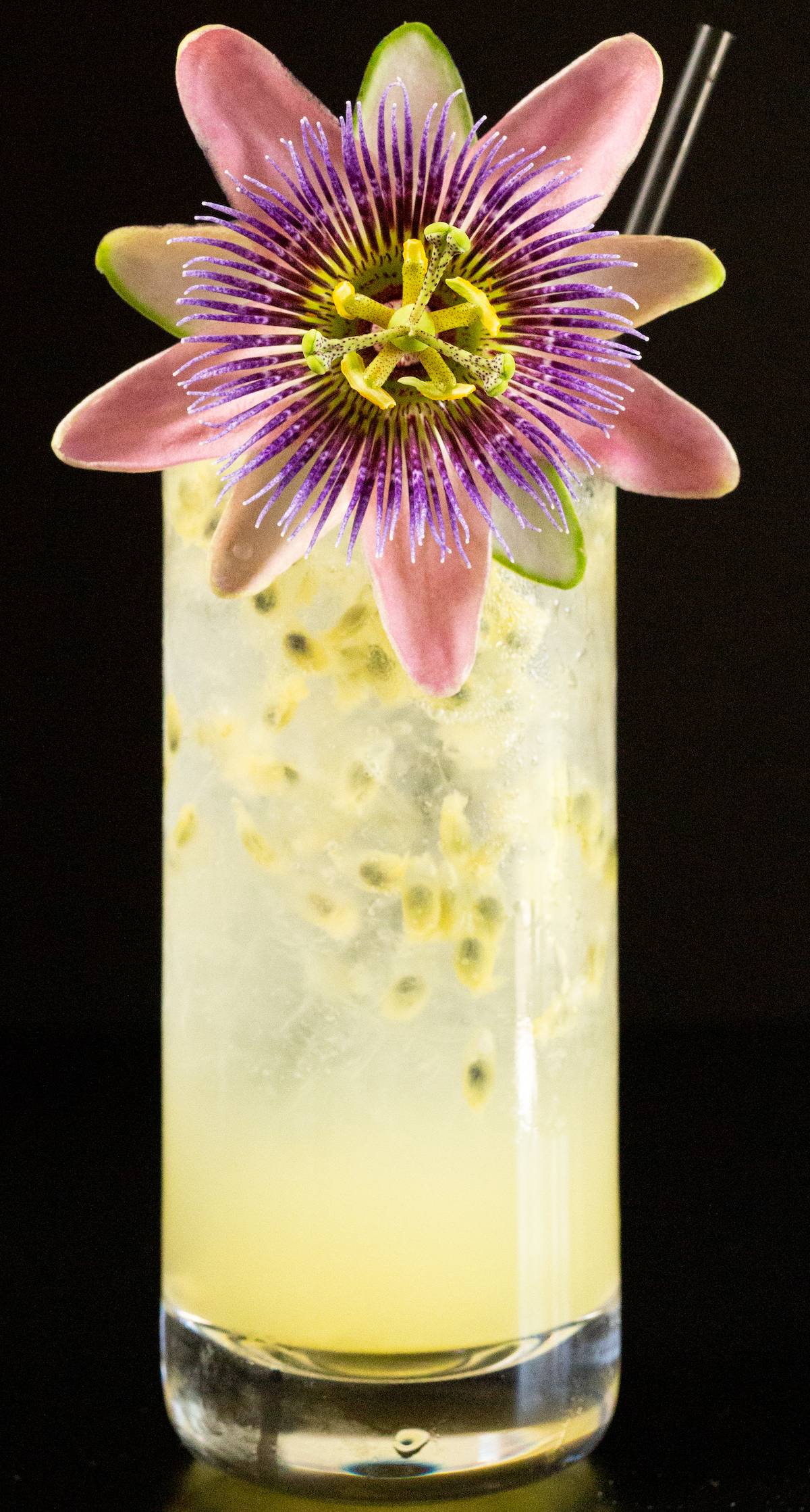 A passion fruit cocktail in a highball glass is garnished with a passion fruit flower