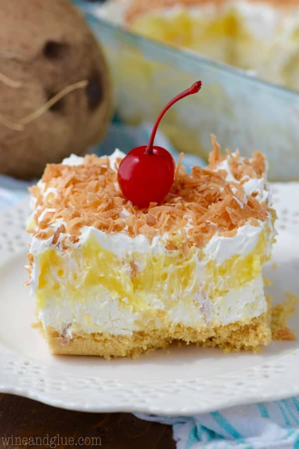 A cut square of Pina colada lush sits on a white serving plate.
