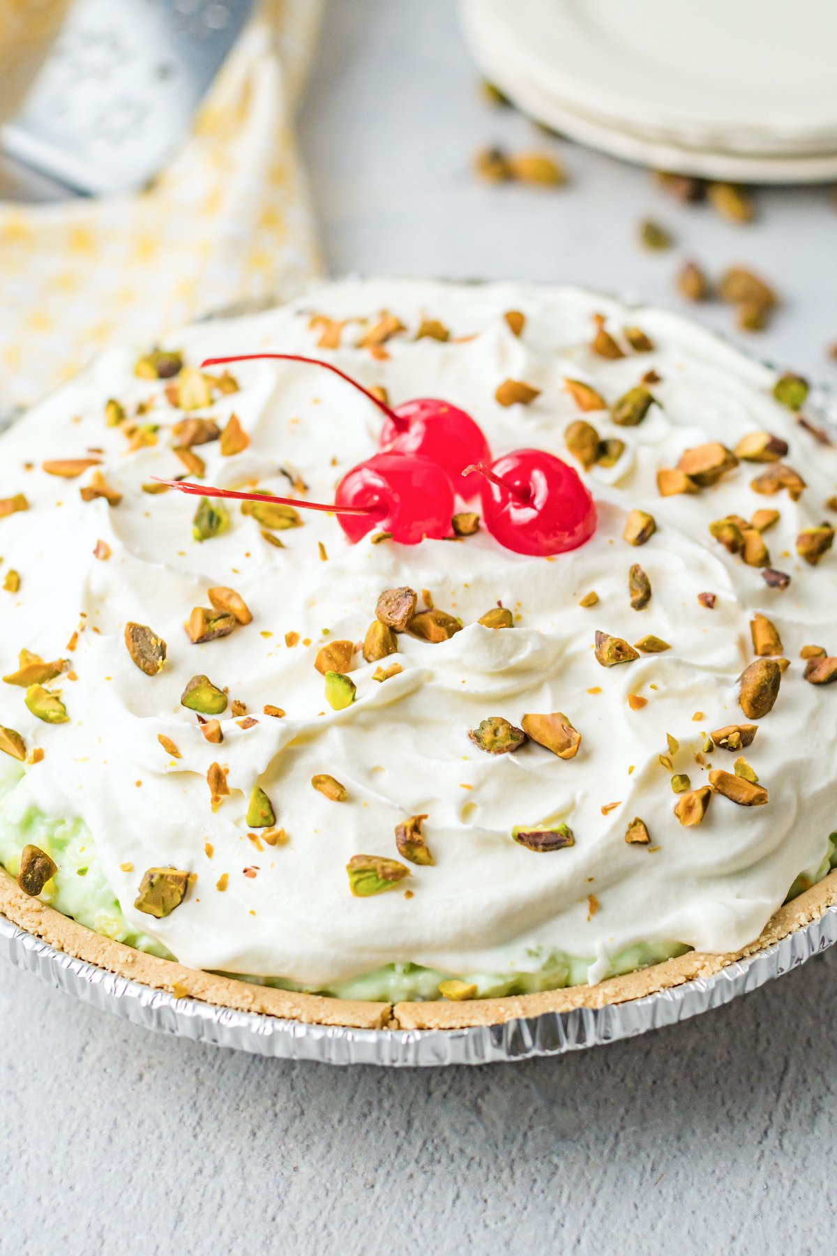 An uncut pistachio pie topped with whipped cream, chopped pistachios, and maraschino cherries.