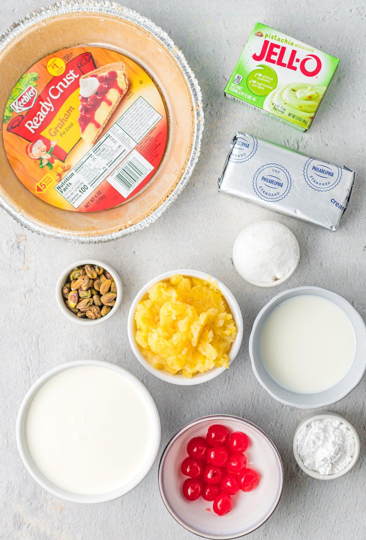 Overhead view of pie ingredients: store-bought graham cracker crust, Jello Pistachio pudding mix, cream cheese, crushed pineapple, sugar, maraschino cherries, chopped pistachios, milk, and heavy cream.