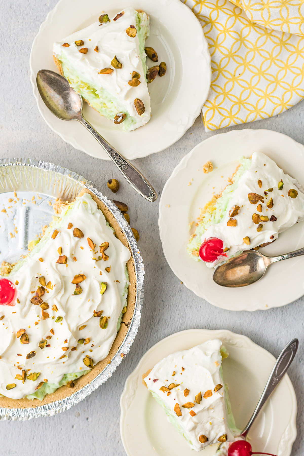 Overhead view of three slices of pistachio pie on serving plates next to the cut pie.