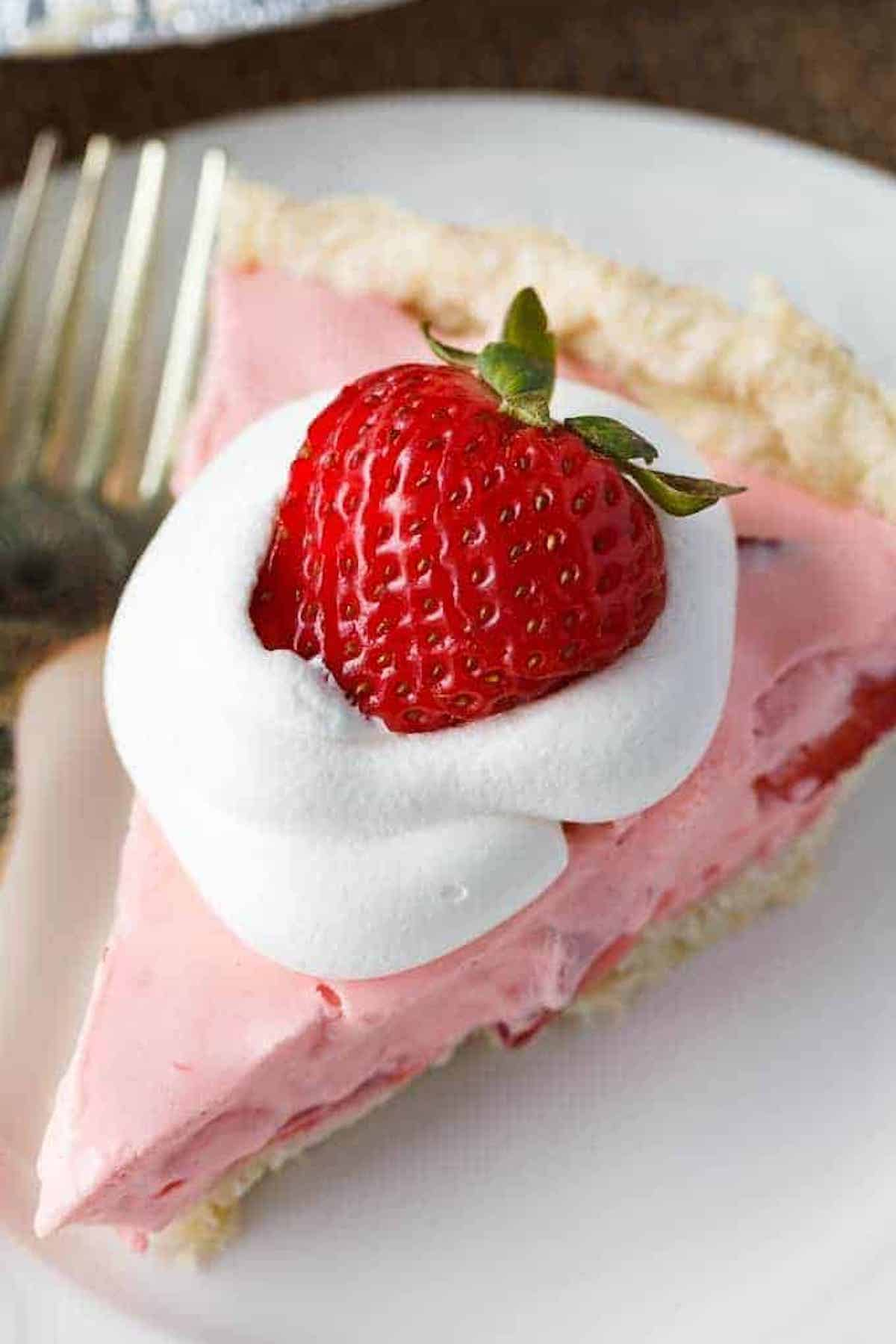 A slice of pink strawberry cream pie garnished with whipped cream and a whole strawberry sits on a white plate.