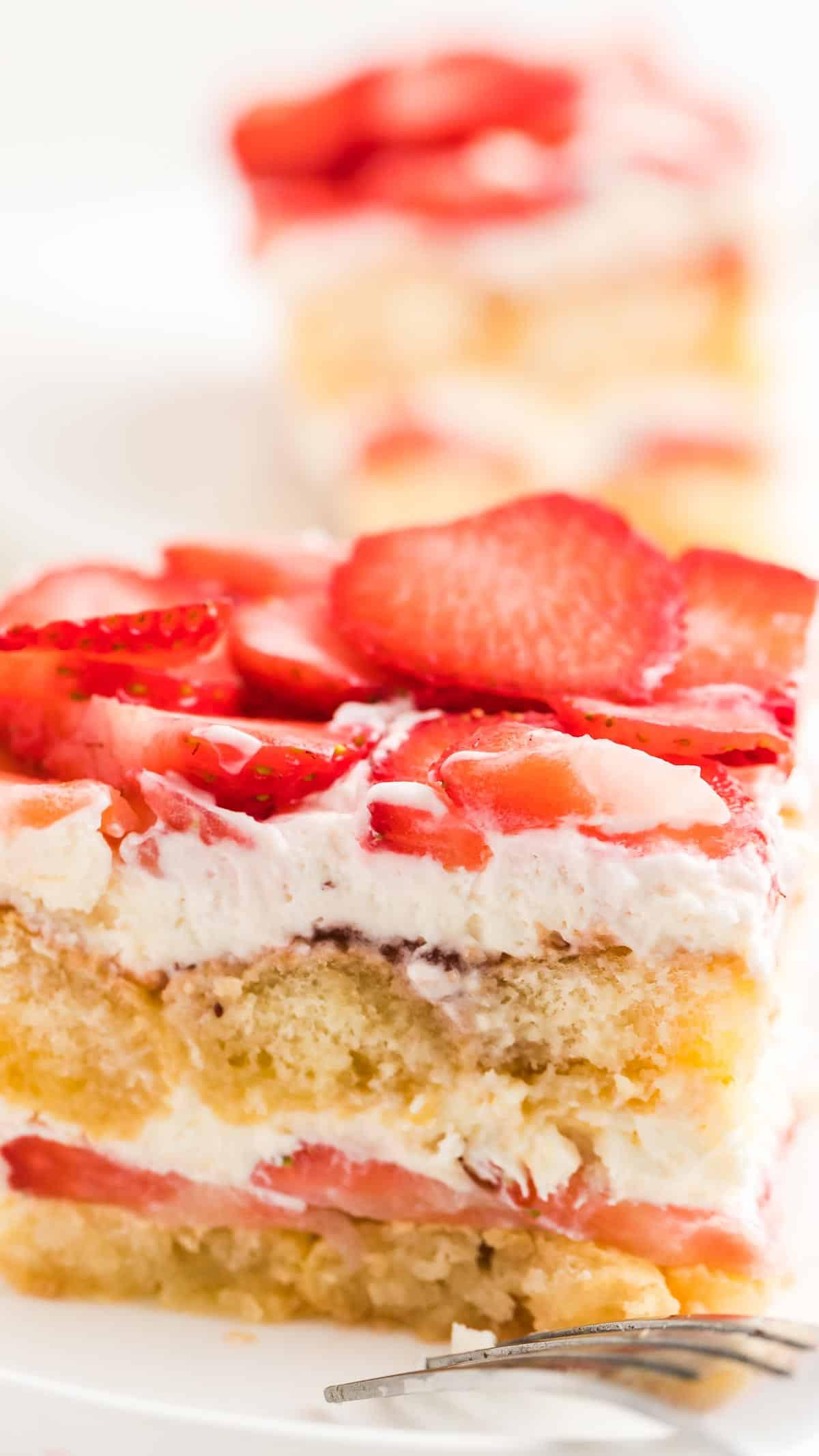 Close up of a cut piece of strawberry tiramisu showing the layers of lady fingers, strawberries, and whipped cream.