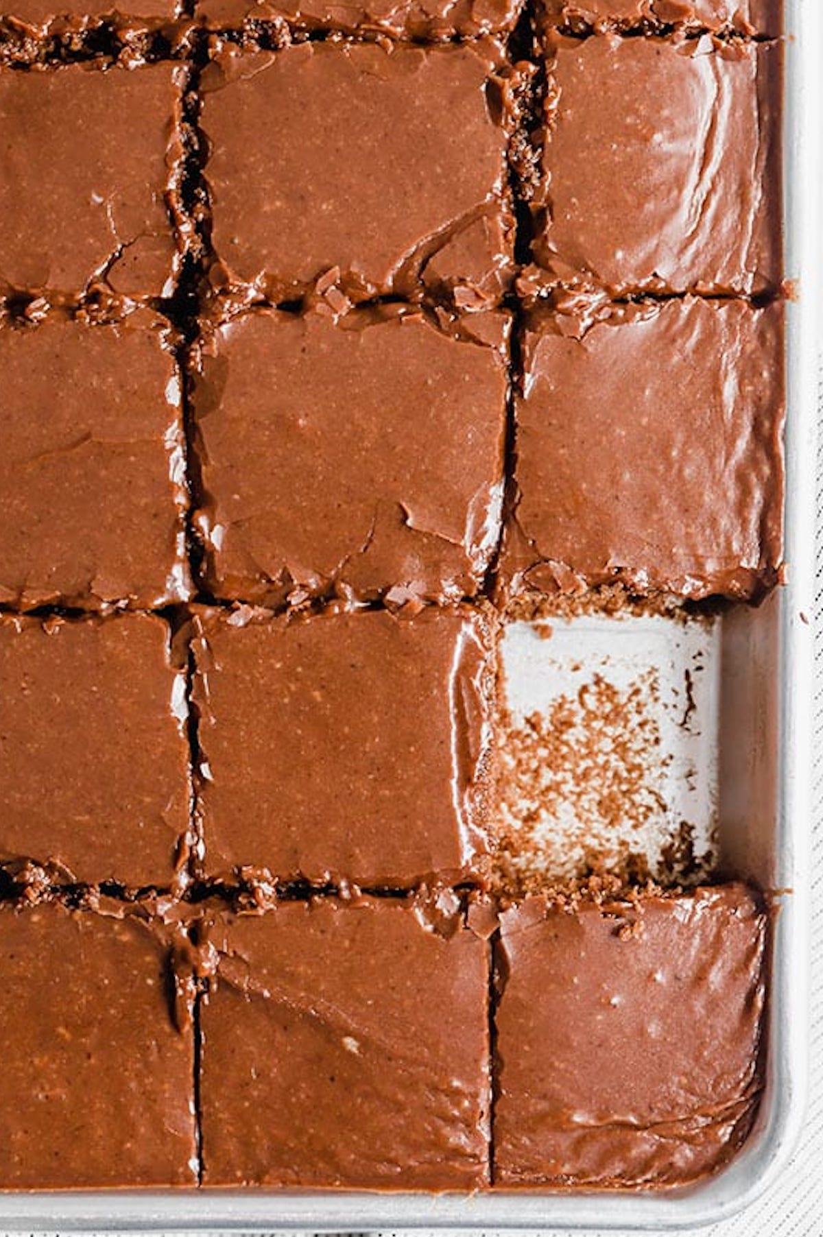 Overhead view of a chocolate Texas Sheet Cake that's been cut into square slices.