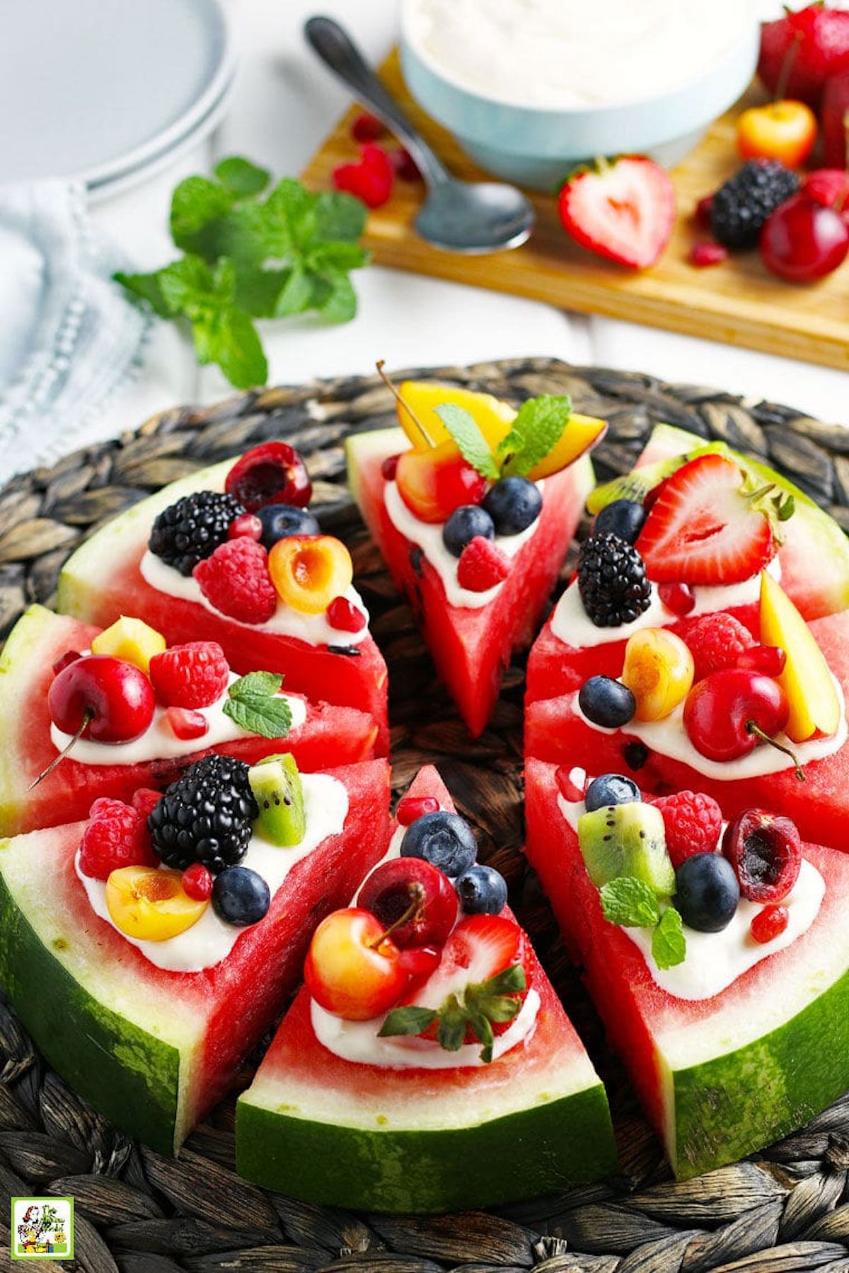 Eight watermelon slices are in the shape of a pizza. Each slice is topped with Greek yogurt then fresh fruit.