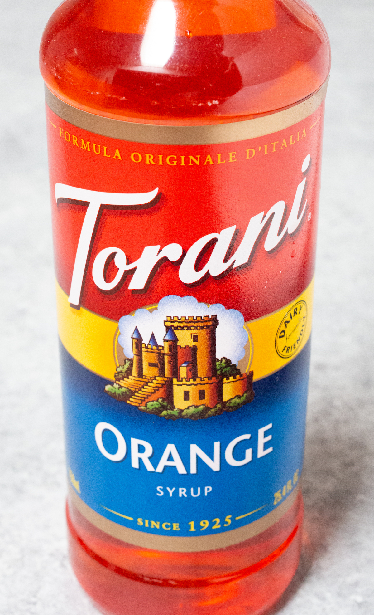 A bottle of Torani Orange Syrup on a light background.
