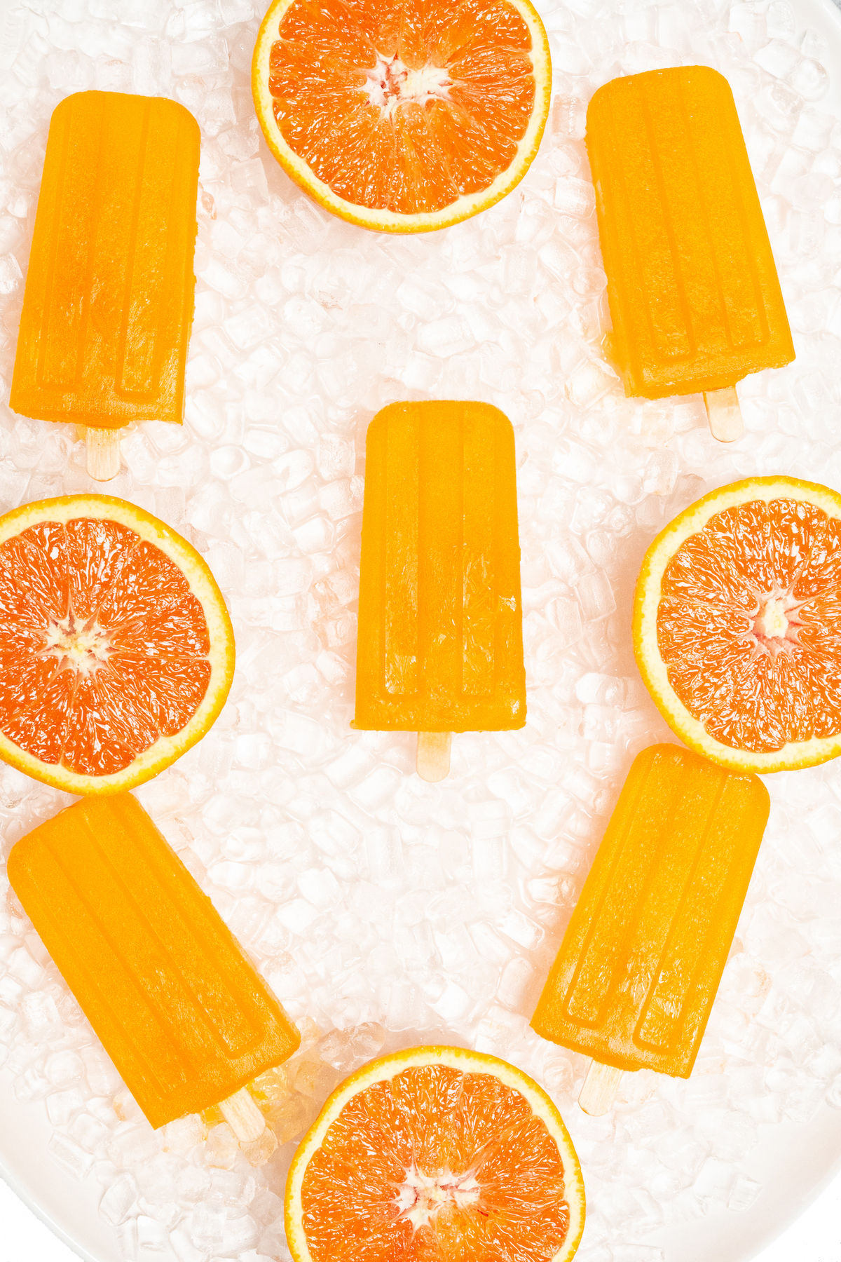Five orange popsicles are arranged on pebble ice on a white platter. They are garnished with oranges sliced in half.